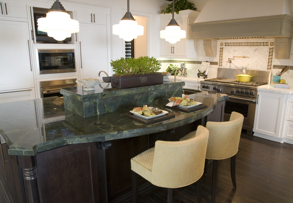 A closer look at this kitchen's large custom island with a stylish countertop and is lighted by large pendant lights.