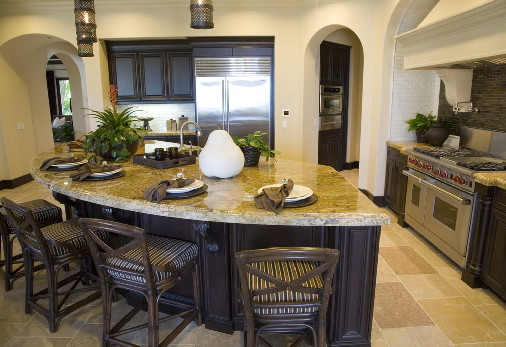 This kitchen features a custom made island with a marble countertop. This kitchen also has a breakfast bar lighted by pendant lights.