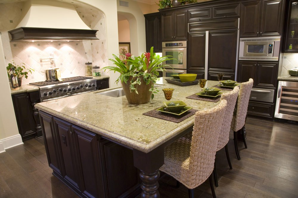 A kitchen with a large island and a breakfast bar counter paired with modish bar seats.