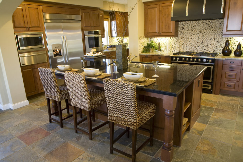 A focused shot at this kitchen's black countertop island with a breakfast bar paired with stylish bar seats.