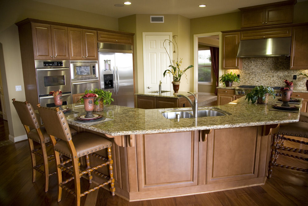 Kitchen boasting a custom granite island with a breakfast bar. This kitchen also has a small square center island.
