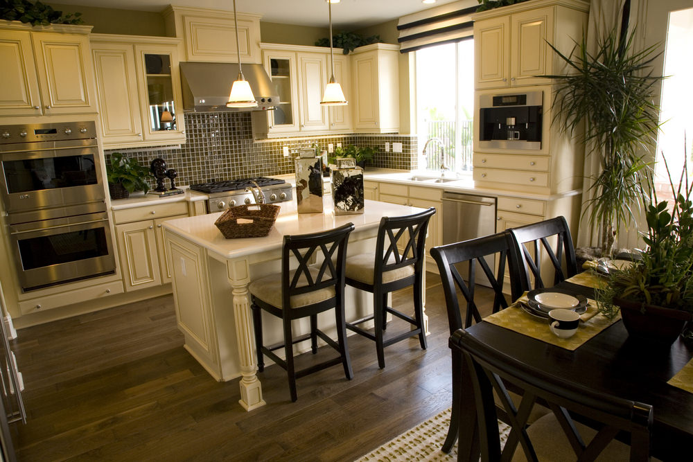 Dine-in kitchen featuring a white island with a breakfast bar along with an espresso-finished dining table set.