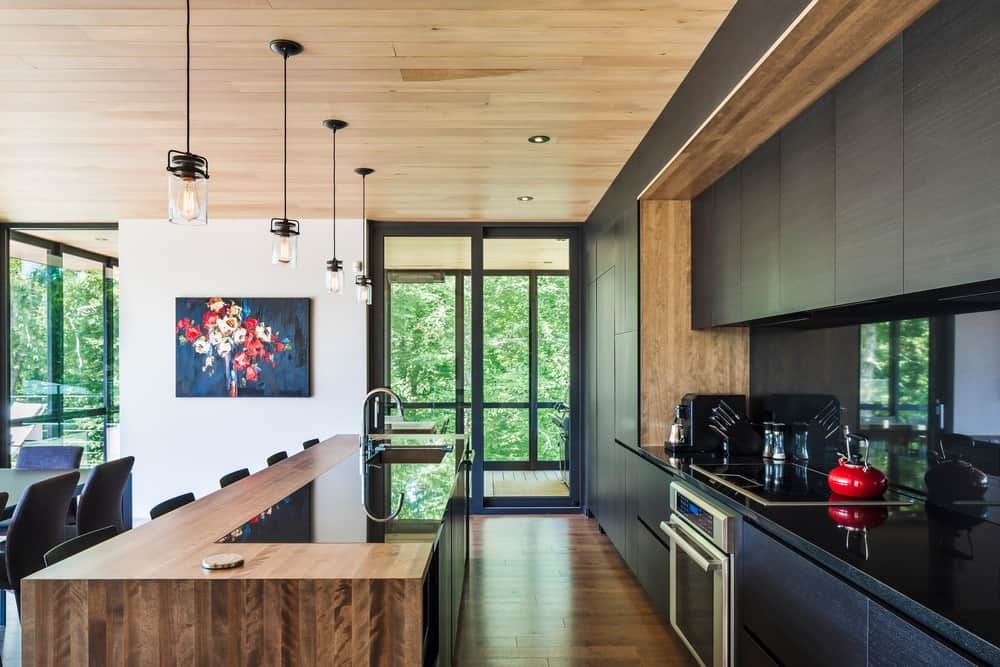 A modern single wall kitchen with a black kitchen counter. It also has a large wooden center island with space for a breakfast bar, lighted by pendant lights hanging from the wooden ceiling.