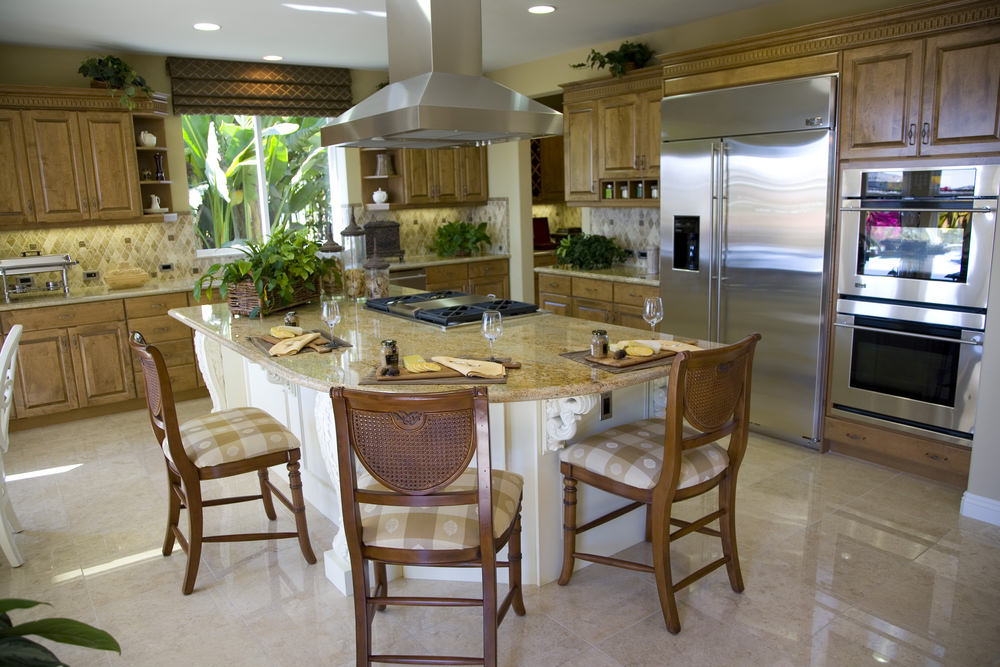 L-shaped kitchen with brown kitchen counters and cabinetry along with a large island featuring a breakfast bar with classy bar seats.