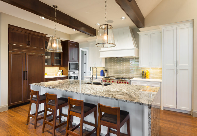 Kitchen with hardwood floors and a ceiling with beams. It offers a waterfall-style marble top island with a breakfast bar lighted by pendant lights.