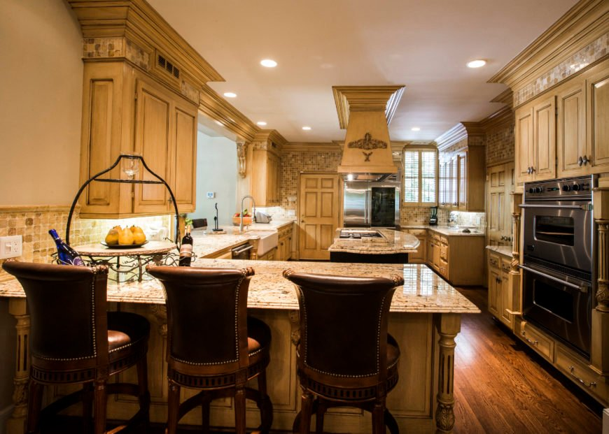 This kitchen offers marble top kitchen counters with a breakfast bar for three. The kitchen features built-in cabinetry as well.