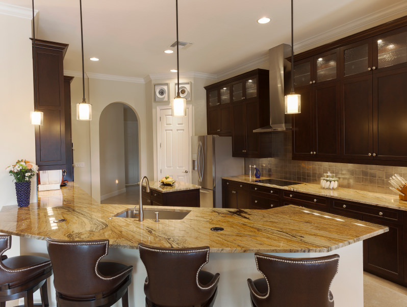 A kitchen with a stunning countertop on this curved island lighted by pendant lights and features classy leather seats.