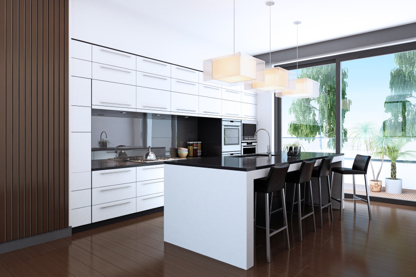 Single wall kitchen featuring hardwood floors and a white ceiling. It has a black countertop on its island with a breakfast bar, lighted by charming pendant lights.