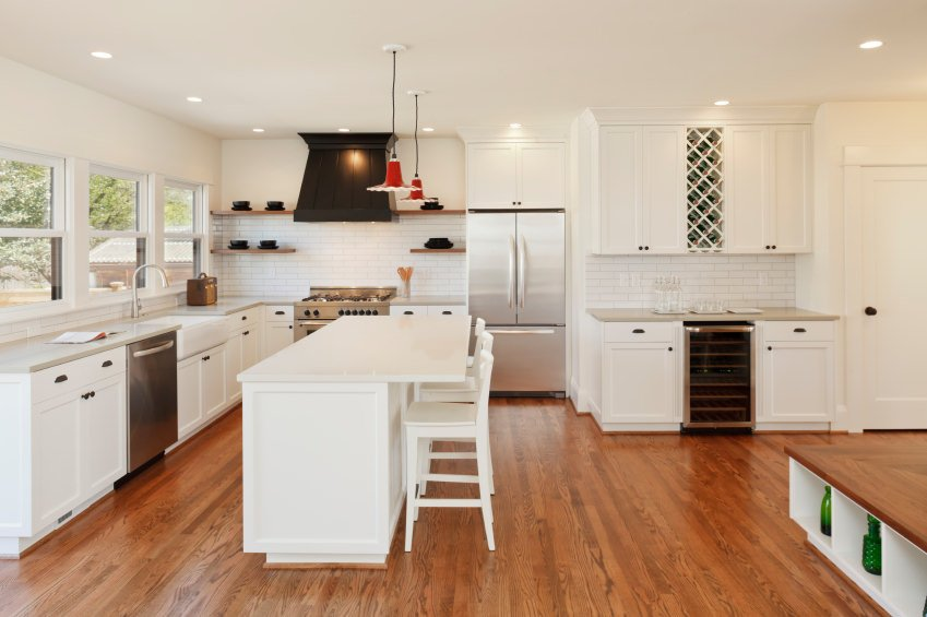 White kitchen with hardwood floors and a white center island with space for a breakfast bar.
