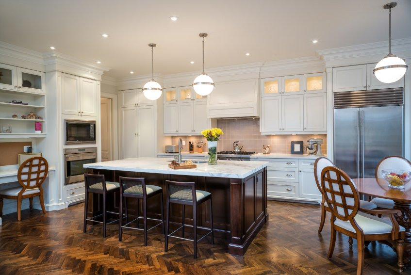 Large dine-in kitchen featuring a stylish herringbone-style hardwood flooring. There's a built-in desk with shelving, a round dining table set and an island with a breakfast bar.