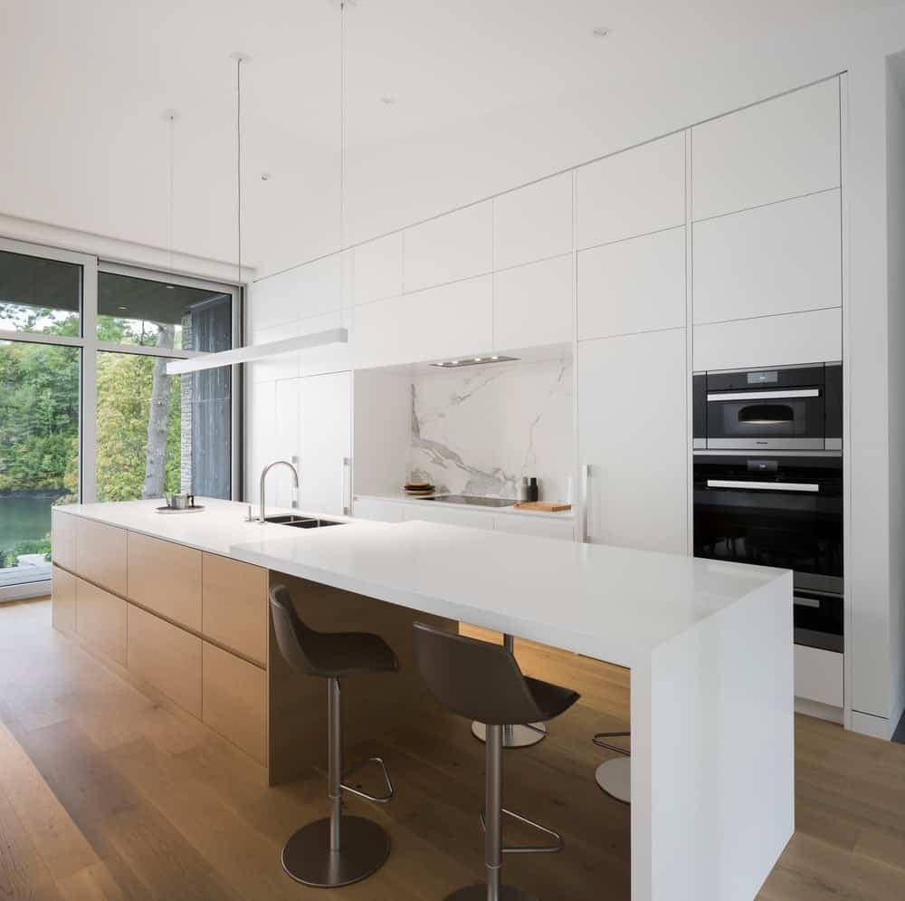 Modern single wall kitchen featuring a marble backsplash and a center island with separate breakfast bar counter.