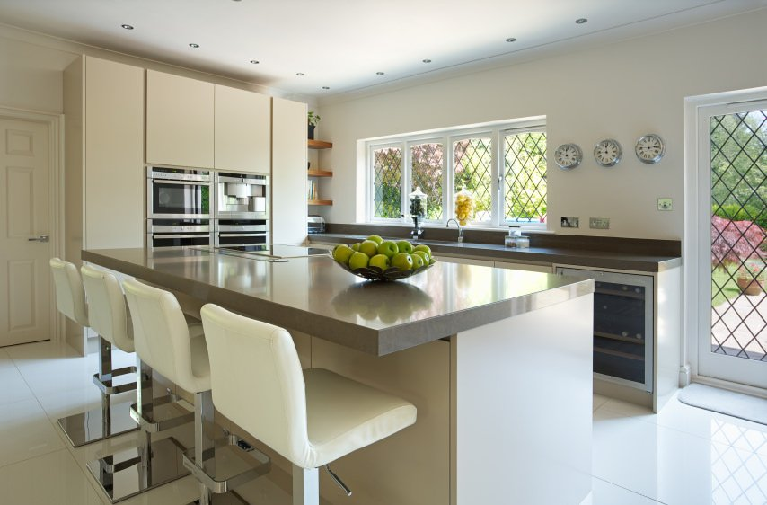 A closer look at this modern kitchen's island with a thick gray countertop. It has a breakfast bar featuring modern bar seats.