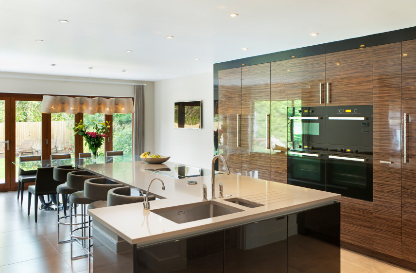Modern kitchen with stylish cabinetry and kitchen counter, along with an island with a breakfast bar and a glass top dining table on the side.