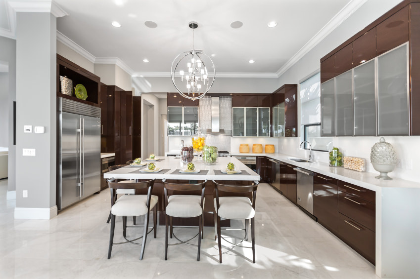 Large modern kitchen featuring stylish kitchen counters and an island with a white countertop lighted by a fancy chandelier.
