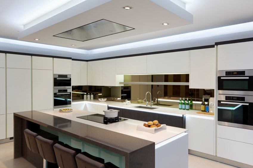 Modern kitchen boasting a stylish island with a separate breakfast bar counter set under the home's gorgeous tray ceiling.