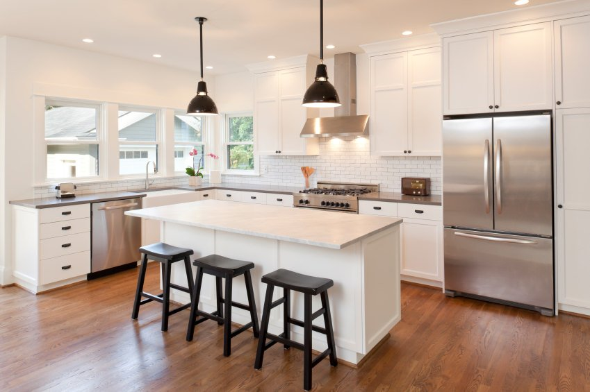 This kitchen offers a white center island with a breakfast bar. The area also features hardwood floors, white walls and a white ceiling.
