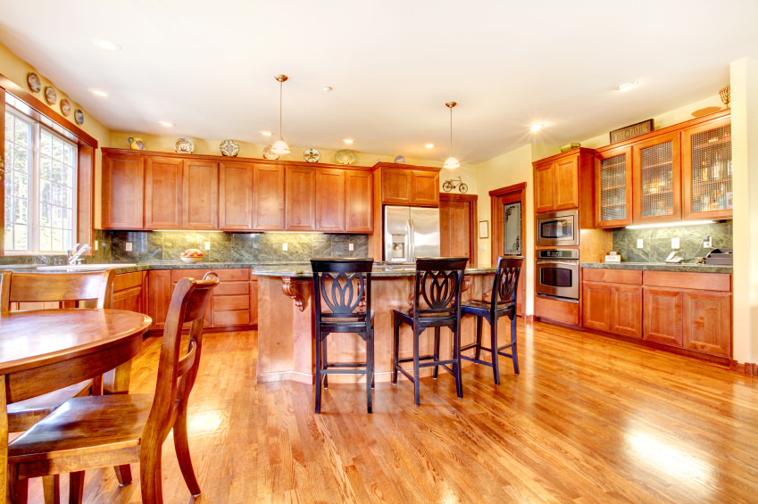 Spacious brown dine-in kitchen featuring a wooden dining table set and an island with a breakfast bar.