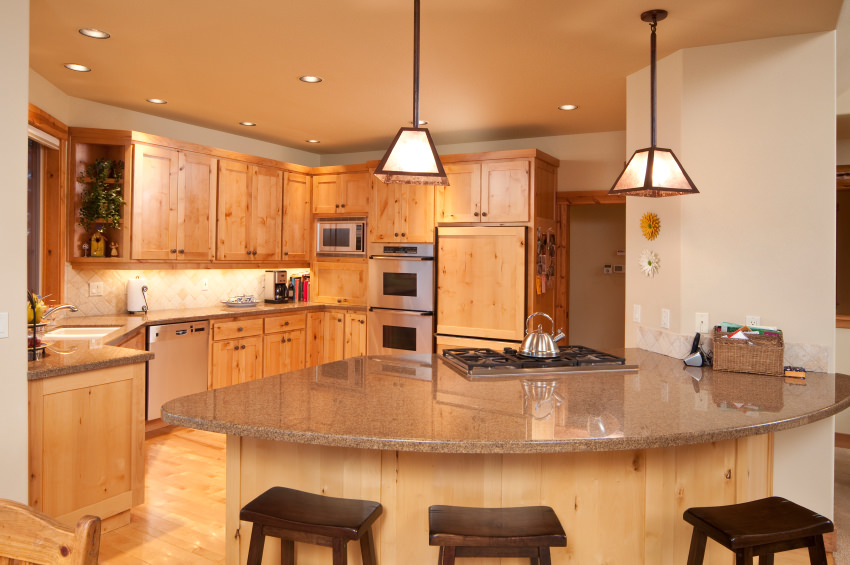This kitchen features brown cabinetry and kitchen counter. It has a breakfast bar island with a granite countertop, lighted by pendant lights.