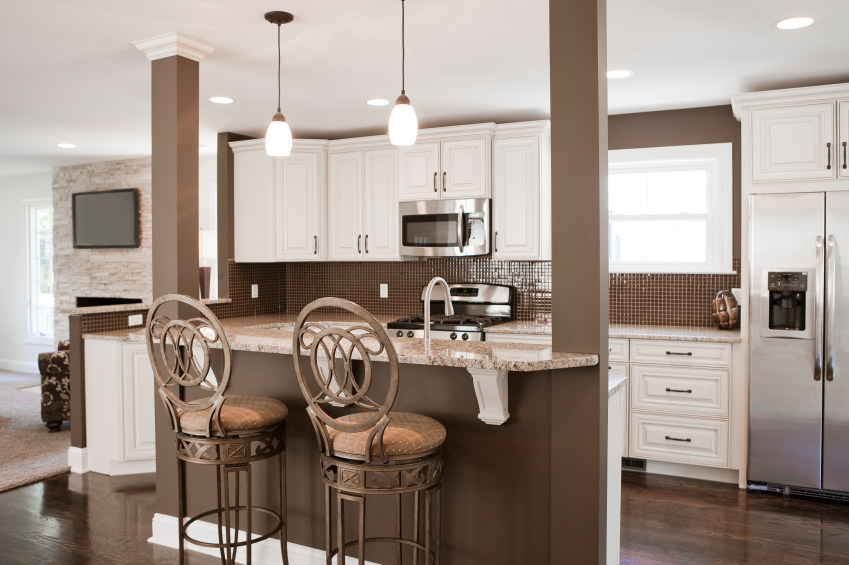 A kitchen featuring a brown and white color scheme. It offers a breakfast bar counter lighted by pendant lights, along with tiny tiles backsplash.