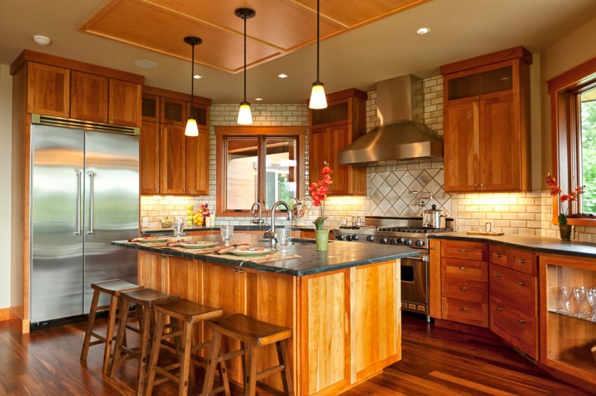 This kitchen features hardwood floors and a stylish ceiling with pendant lights just above the center island with a breakfast bar.