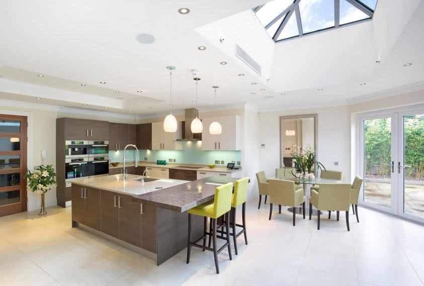 Large modern dine-in kitchen featuring an island with a built-in breakfast bar counter lighted by pendant lights, along with a round dining table set on the side.