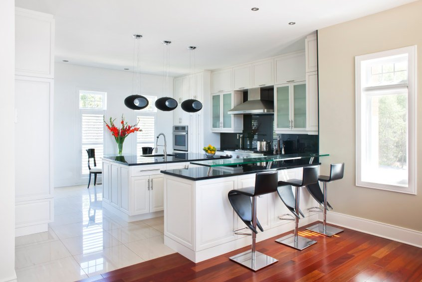 A white kitchen featuring a center island and an island with black countertops and has a glass breakfast bar counter.
