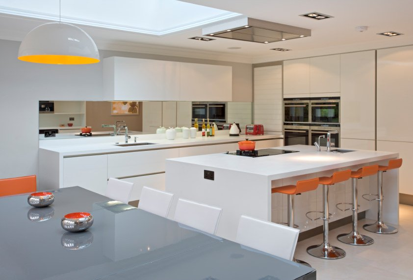 Modern kitchen boasting a white kitchen counter and a large white breakfast bar island, along with a gray dining table set. The area features tiles flooring and a ceiling with skylight.