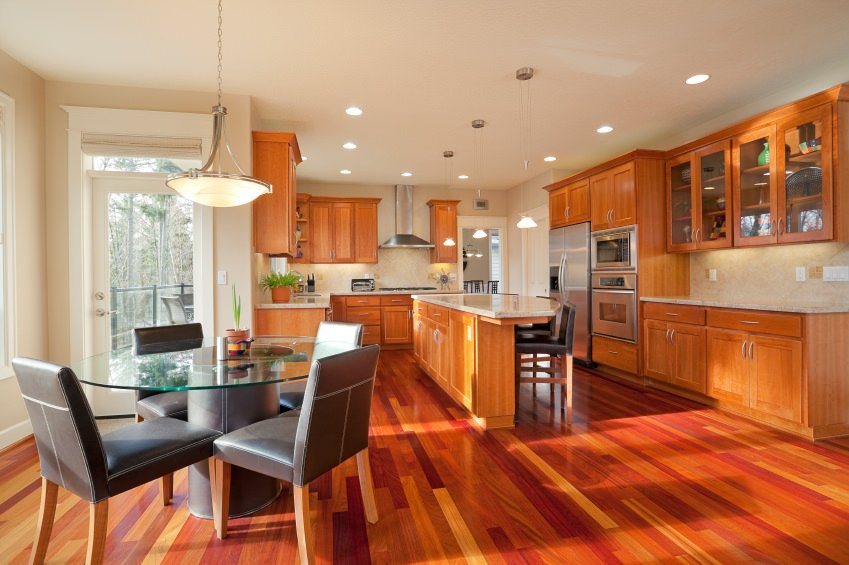 A spacious dine-in kitchen with stylish hardwood flooring and a white ceiling. It offers a breakfast bar and a round dining nook table set lighted by a pendant light.