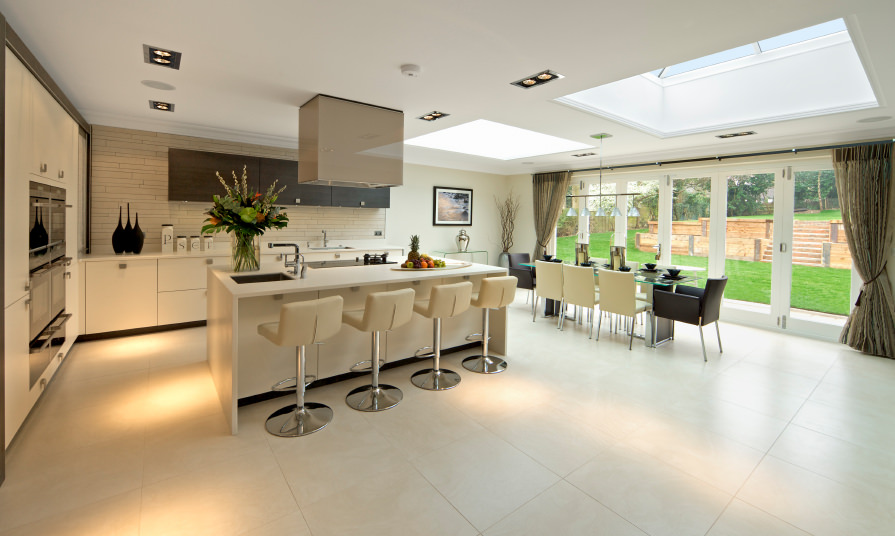 Large dine-in kitchen featuring a modern glass top dining table set and a white island with a breakfast bar paired with modern bar seats. The area features tiles flooring and a ceiling with skylights.