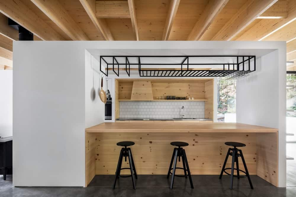 A modern galley kitchen featuring a wooden breakfast bar counter surrounded by white walls.