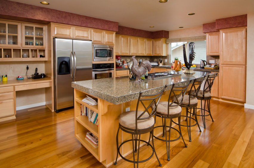 This kitchen features a built-in desk and a granite top island with built-in shelving and has space for a breakfast bar.