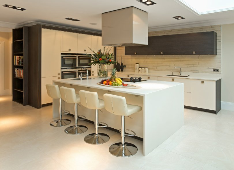 Small modern kitchen area offering a large white island with a breakfast bar paired with modern white bar seats. The ceiling also features a large skylight.