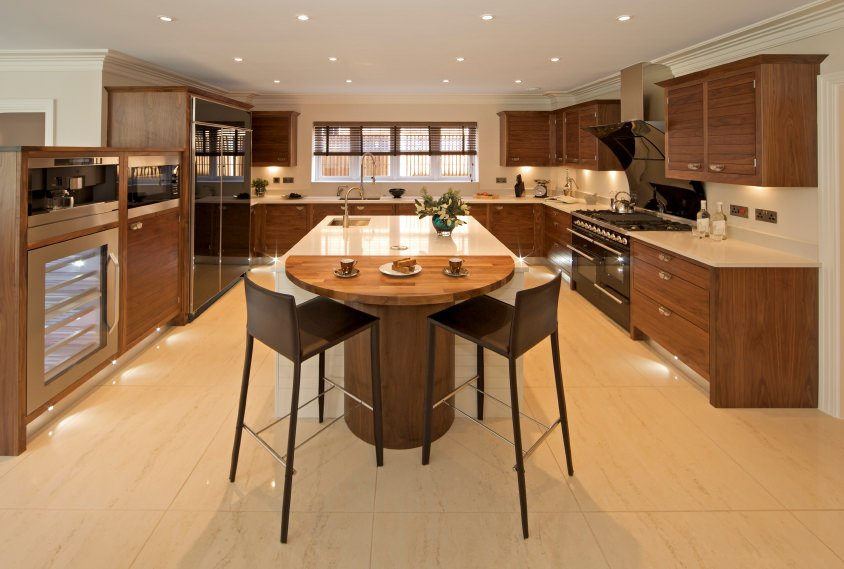 Large kitchen area with modern brown cabinetry and kitchen counters. It offers a white center island together with a wooden breakfast bar counter for two.