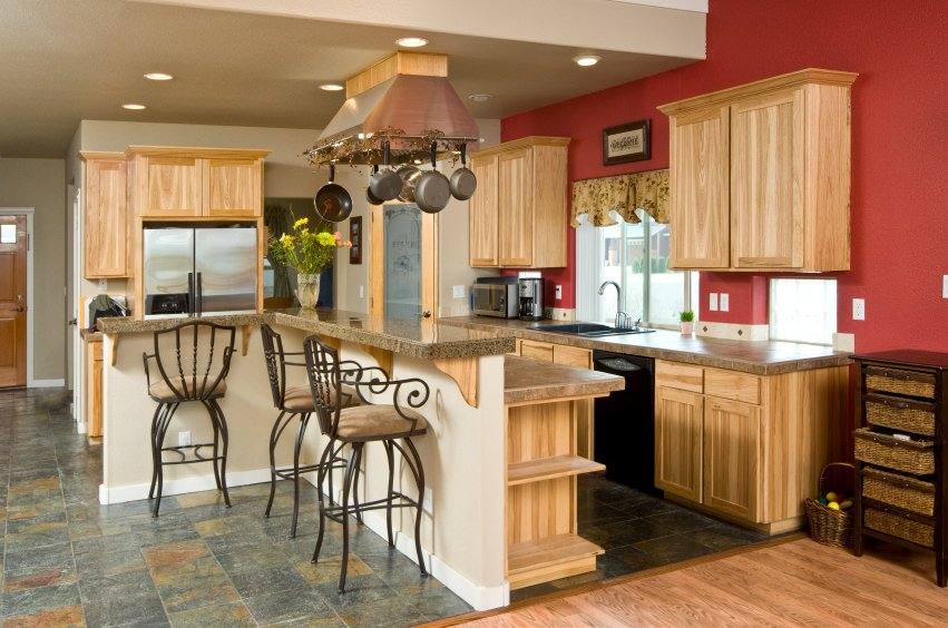 L-shaped kitchen with walnut-finished cabinetry and kitchen counters. It has a custom island with a granite breakfast bar counter.