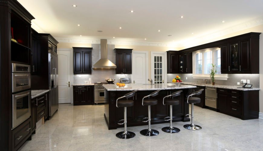 Spacious kitchen boasting espresso-finished cabinetry and kitchen counters. The marble countertops add style to the kitchen. There's a breakfast bar as well equipped with modern bar seats.