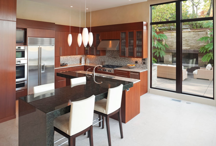 Small kitchen area with a black granite breakfast bar island along with brown cabinetry and kitchen counters. The area is lighted by attractive pendant lights.