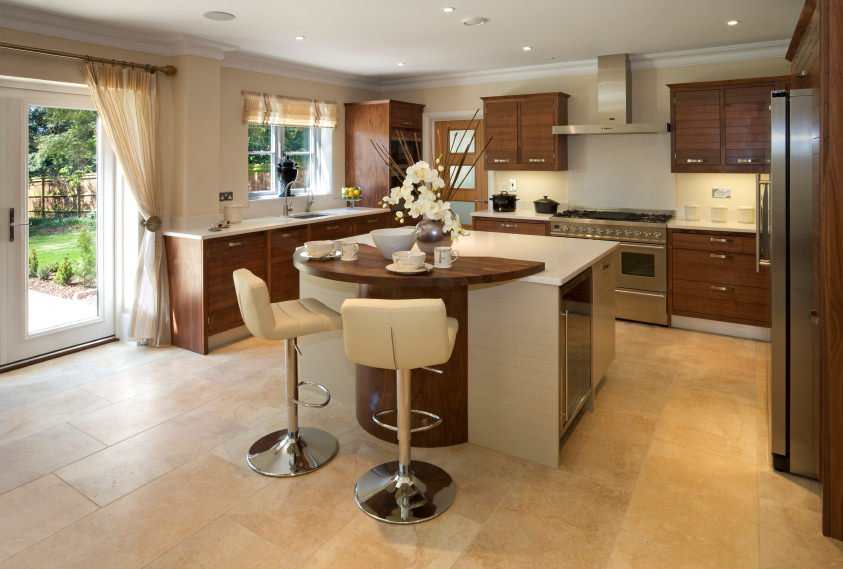 A modern kitchen featuring a white center island with a wooden breakfast bar counter paired with modern bar seats.