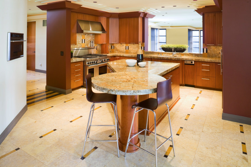 This kitchen features a custom made island with a round breakfast bar counter, made of granite countertops. The home also features decorated floors and ceiling.