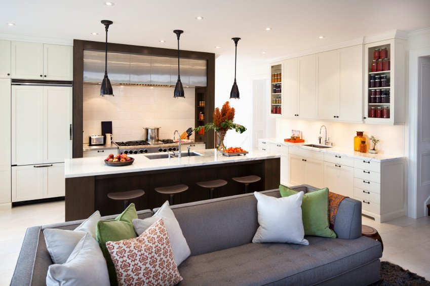 Modern great room boasting a living space with a gray couch along with a kitchen with a white countertop island featuring a breakfast bar.