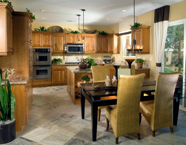 This kitchen offers brown kitchen counters and cabinetry, along with a center island with granite countertop. There's a rectangular dining table set as well.