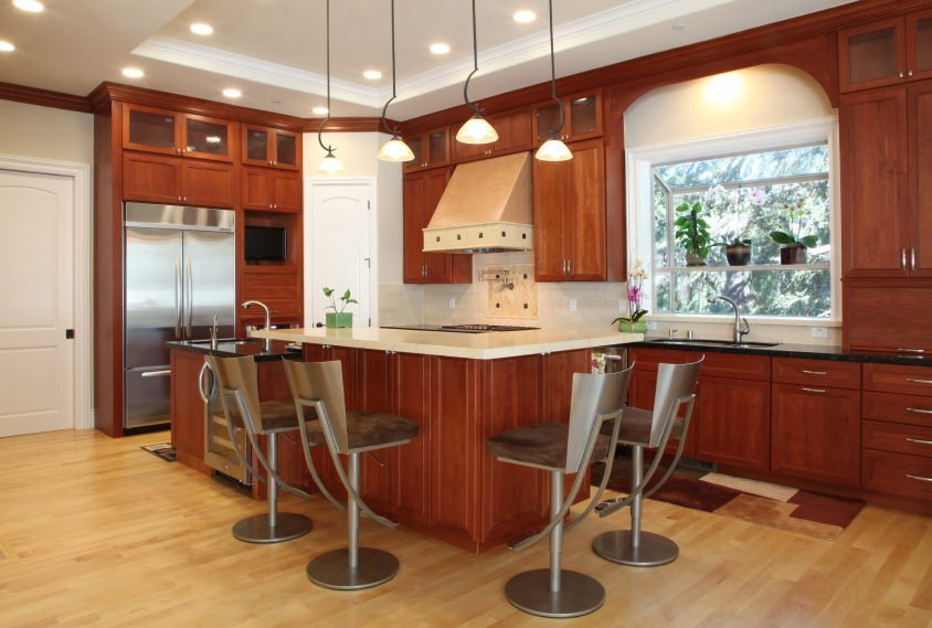 Small kitchen area with an L-shaped breakfast bar paired with modern bar seats. The area features a white tray ceiling with recessed and pendant lights.