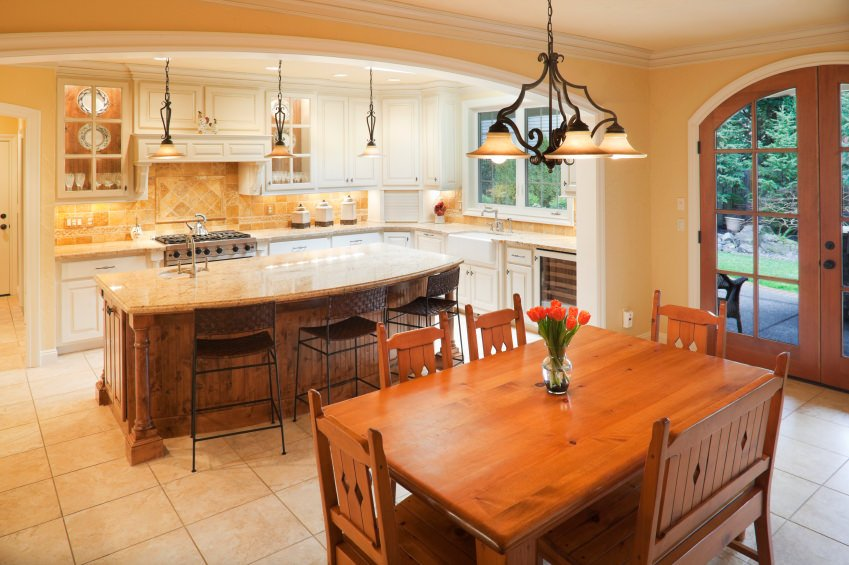 A dine-in kitchen with a wooden dining table set and a large center island offering space for a breakfast bar.