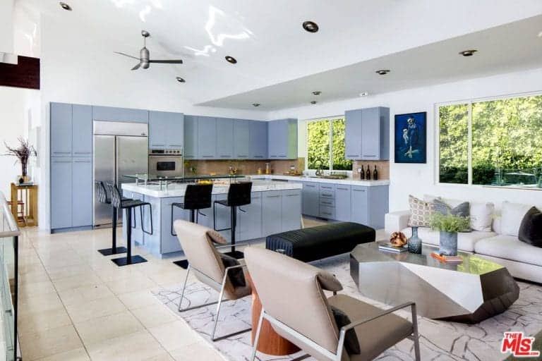 This great room boasts a cozy living space and an L-shaped kitchen with blueish gray kitchen counters and cabinetry. It also has a large center island with a marble countertop and has a breakfast bar.