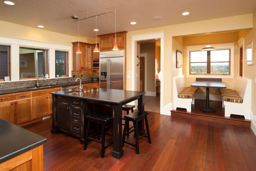 A spacious dine-in kitchen with reddish hardwood floors, beige walls and a regular ceiling. It offers a breakfast bar island and a dining nook on the side.