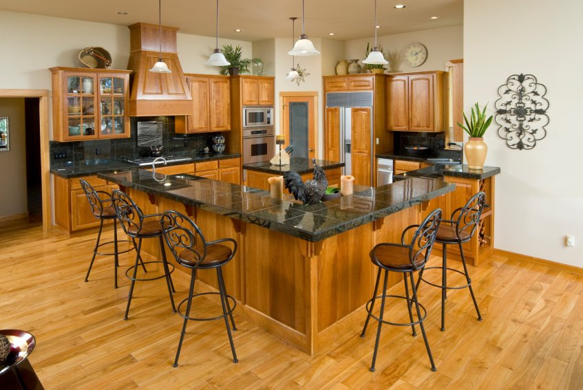 Small kitchen area with black countertops. It has a small square center island and an L-shaped breakfast bar counter with pendant lights.