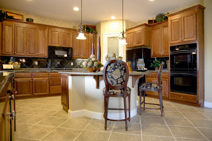 This kitchen features brown cabinetry, brown kitchen counters and a center island with a granite countertop and has a breakfast bar paired with elegant bar seats.