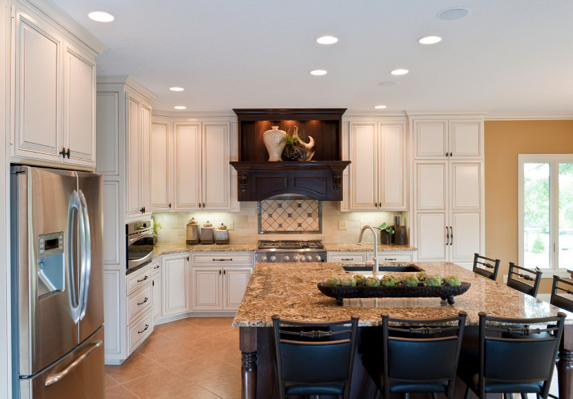 L-shaped kitchen with brown tiles flooring and a white ceiling lighted by recessed ceiling lights. The kitchen offers a large square center island with a marble countertop.