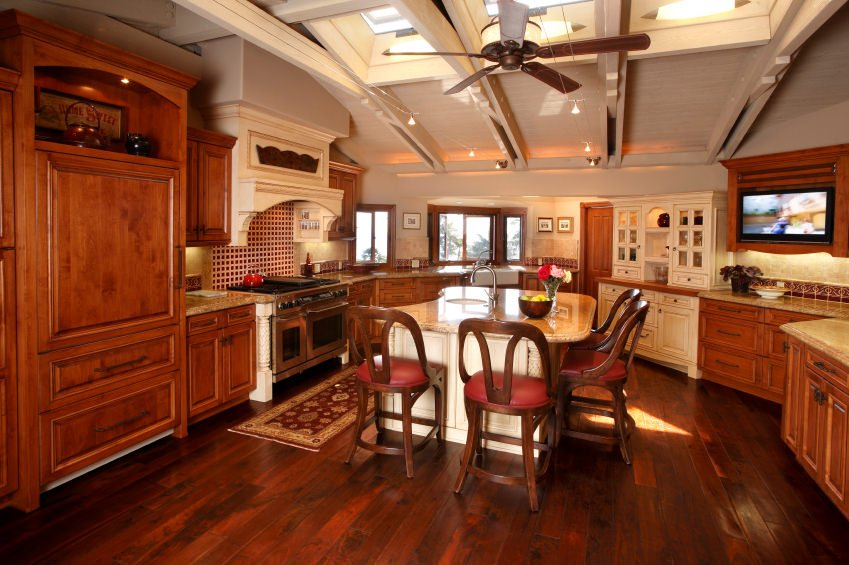 A spacious kitchen with hardwood flooring and a stunning ceiling with skylights. There's a center island with a breakfast bar as well.