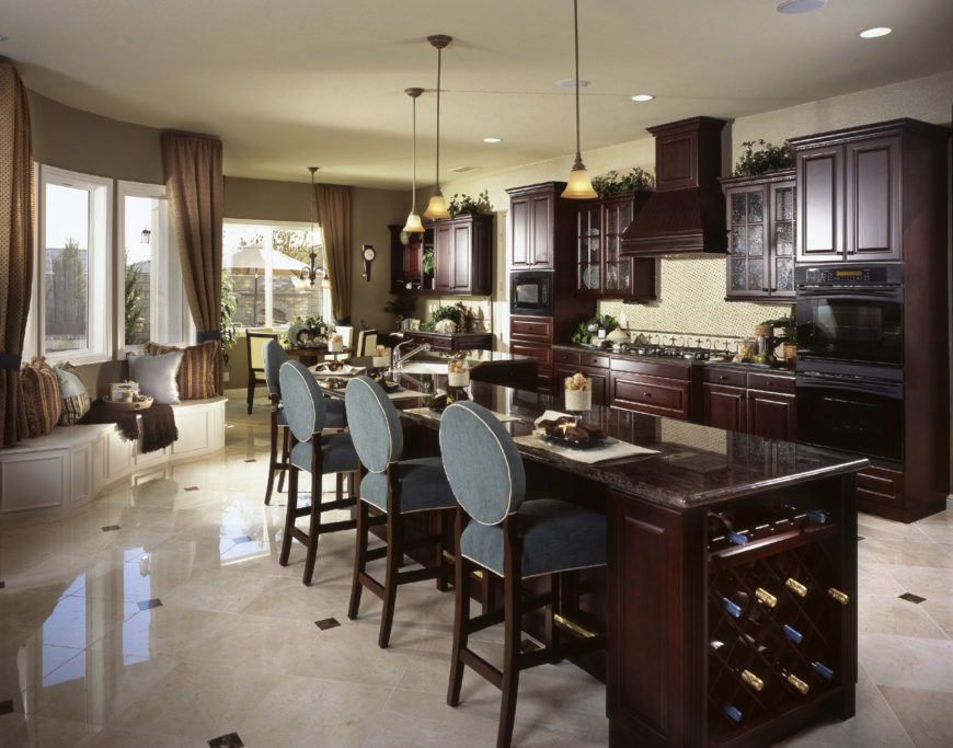 A spacious kitchen with classy tiles flooring and gray walls. It offers a long breakfast bar island with a built-in wine cellar and is lighted by pendant lights.