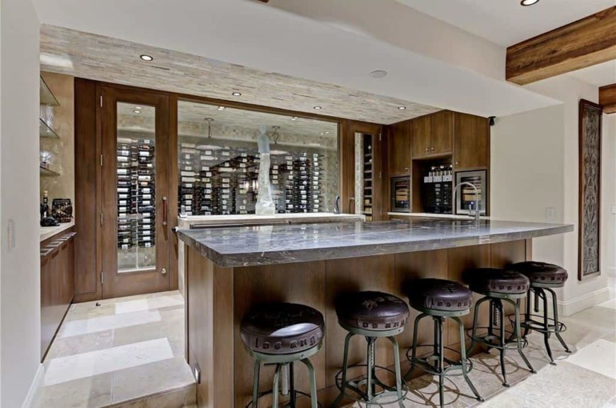 This kitchen also offers a modern wine cellar and has a bar counter featuring a thick gray countertop paired with classy bar stools.